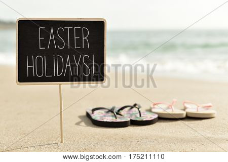 closeup of a chalkboard with the text easter holidays written in it and a pair of colorful flip-flops on the sand of a lonely beach