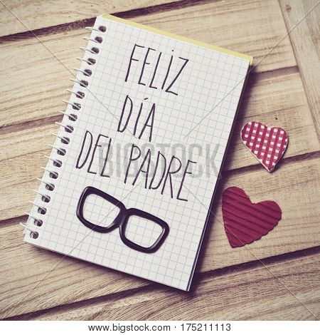 the text feliz dia del padre, happy fathers day in spanish written in the page of a notebook, a pair of black eyeglasses and some red hearts on a rustic wooden background