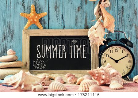 closeup of a chalkboard with the text summer time, an alarm clock, many conches and starfishes, and a beach pail, on a pile of sand, against a bright blue rustic wooden background