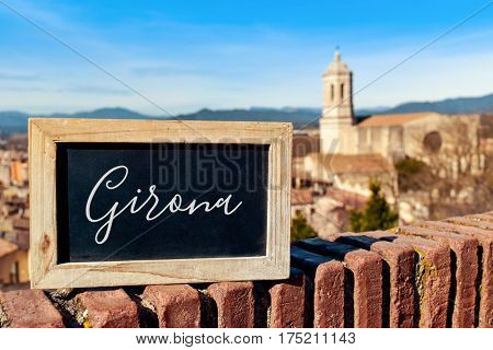 closeup of a chalkboard with the word Girona written in it in Girona, Spain, seen from above highlighting the Cathedral on the right