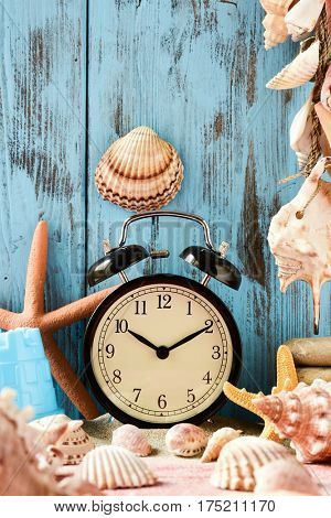 closeup of an alarm clock, many different conches and starfishes, and a beach pail, on a pile of sand, against a bright blue rustic wooden background