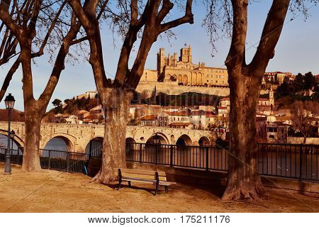 a view of the Pont Vieux bridge above the Orb River in Beziers, France, with the Old Town on the right, highlighting the Cathedral of Saint Nazaire