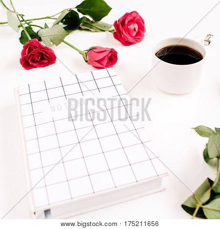 Red roses flowers coffee cup notebook and clips on white background. Top view. Feminine background.