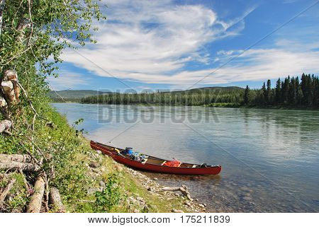 Red towed and abandoned canoe on Yukon River