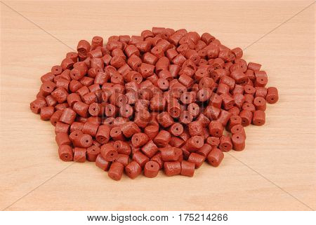 Red pre-drilled halibut pellets for carp fishing isolated on wood background with soft shadow