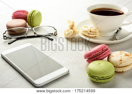 Cup of black tea with tasty varicolored macaroons smartphone glasses on a white background in light key.