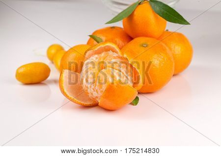 Peeled ripe tangerine in front of other tangerines on a white surface