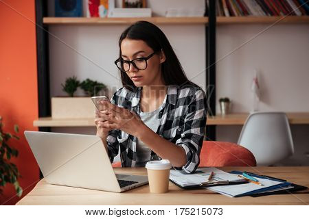 Image of beautiful young caucasian lady wearing glasses sitting indoors while using mobile phone and laptop computer. Coworking concept.