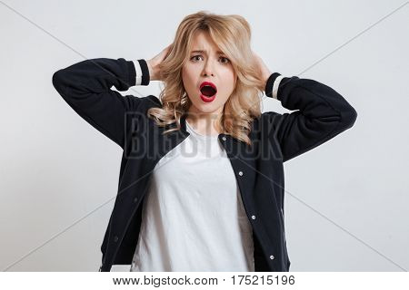 Portrait of a surprised astonished young woman looking at camera isolated on the gray background