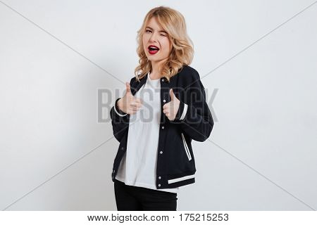 Portrait of a playful pretty girl in casual clothes showing two thumbs up isolated on the white background