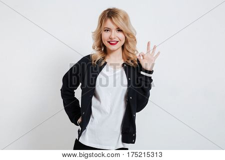 Smiling cheerful girl in casual clothes showing okay sign isolated on a white background