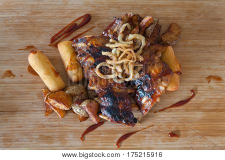 American grilled ribs on the grill topped with barbecue sauce with onion rings and hot crispy potatoes with mashed potato-filled croquettes - American food - fast food