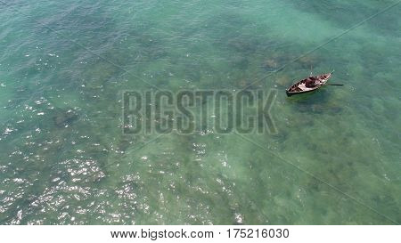 Aerial top view of sea and fisherman on the boat