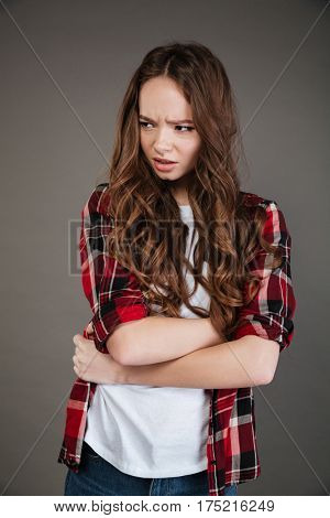 Angry irritated young woman in plaid shirt standing with arms crossed over grey background