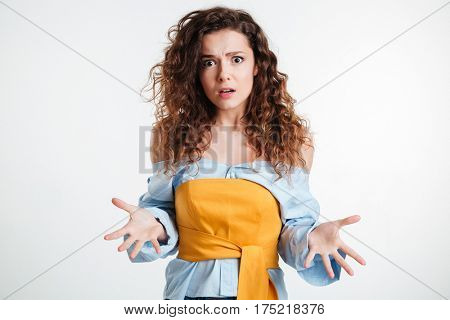 Amazed confused young woman gesturing with hands over white background