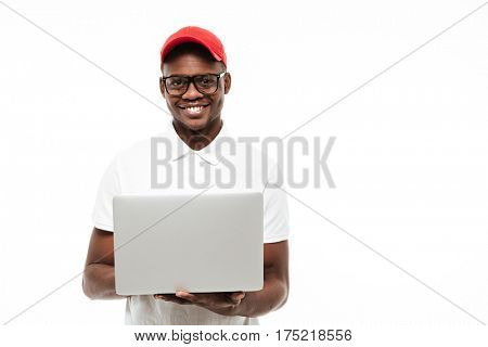 Photo of cheerful young african man wearing cap isolated over white background using laptop computer. Looking at camera.
