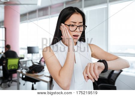 Amazed shocked asian young businesswoman looking at wristwatch in office
