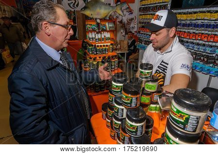 Moscow, Russia - February 25, 2017: Gray-haired respectable man buys bait for fishing on the special exhibition in VDNKh