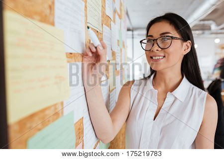 Happy pretty asian young woman in glasses writing advertisement on bulletin board