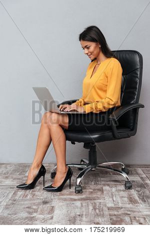 Full length portrait of a smiling successful woman sitting on chair and working on laptop computer isolated over gray background