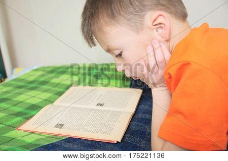 children education kid reading book lying on bed serious child read with book education concept interesting fairy tale