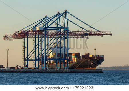 Loading of containers by port cranes to a transport ship in the port of Odessa. Ukraine. Black Sea.