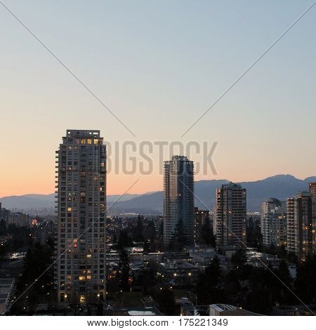 Cityscape And Mountains At Sunset