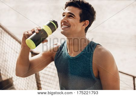 Close up shot of happy young man drinking water after workout outdoors. Fit male runner resting after training session and laughing.