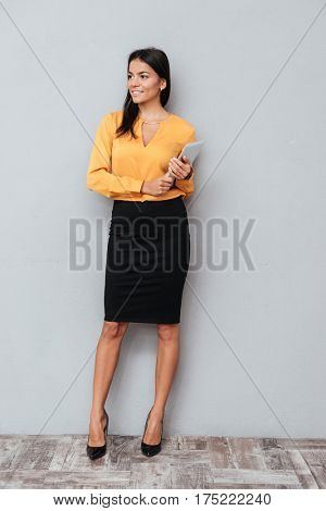 Full length portrait of a confident young business woman standing and holding digital tablet isolated against gray background
