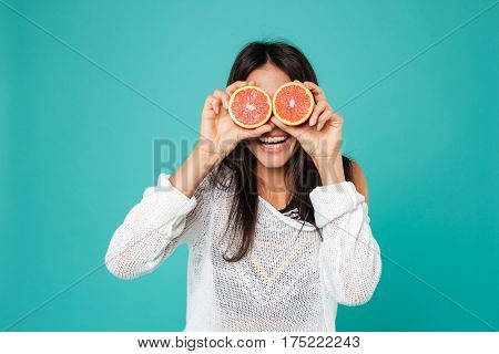 Funny playful young woman holding grapefruit halves in front of her eyes over blue background