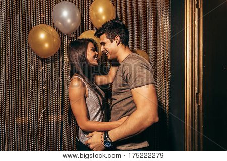Shot of romantic young couple in the night club. Young couple having good times in the party at pub.