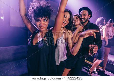 Group of friends dancing in night club. Young men and women having fun at disco club.