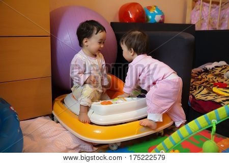 Two baby girl twin sisters playing together