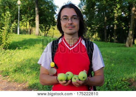 Handsome man with green apples in garden