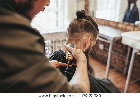 Man getting haircut by barber at salon. Hairdresser cutting hair of client with hair trimmer machine.