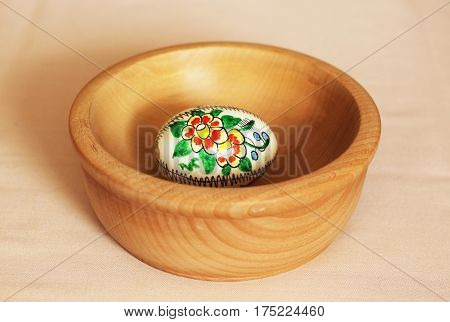Easter egg with painted red and yellow flower in the wooden bowl