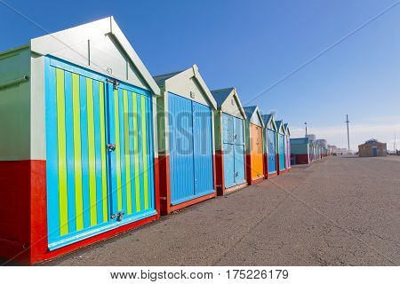 Lots of very colorful bathing huts in Brighton and Hove and people walking the attraction British Airways i360 in the background