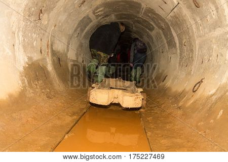 Group Of Tourists Under The Ground. Tourists In The City Sewers.