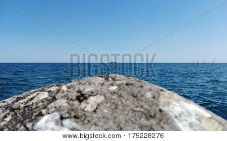 Landscape of grey stone with white small shells at the port seaside the blue wave ocean sea with clearly blue sky the small boat transports in the sea