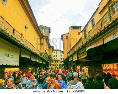 Florence, Italy - May 01, 2014: people in shopping area on Ponte Vecchio or Old Bridge in Florence. The Ponte Vecchio is medieval stone bridge noted for still having shops built along it