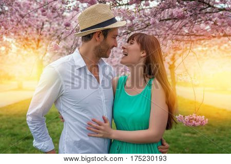 couple outdoors walking with cherry blossom
