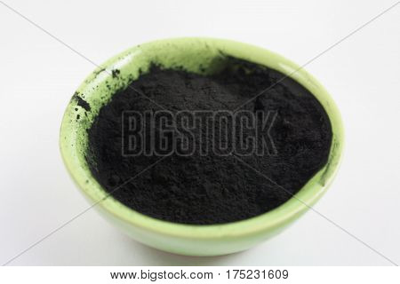 Black activated charcoal powder in a bowl