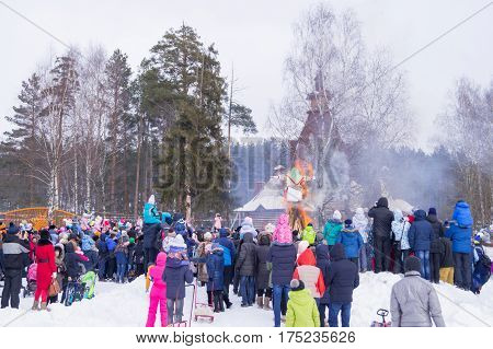 Kostroma, Russia - Febrary 26, 2016: Straw Scarecrow of Shrovetide before burning on Mardi Gras celebration, pancake week. Adults and children celebrate end of winter and beginning of spring