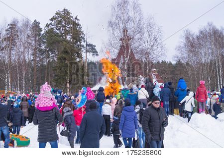 Kostroma Russia - Febrary 26 2016: Straw Scarecrow of Shrovetide before burning on Mardi Gras celebration pancake week. Adults and children celebrate end of winter and beginning of spring