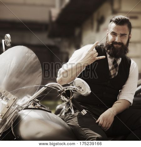 Serious Bearded Biker Man in black jacket sitting on motorbike outdoors
