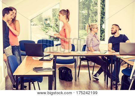 Highschool students having fun during a break in classroom interior