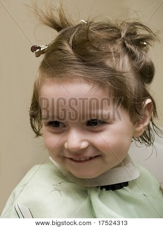 Small girl at hairdresser's wearing hairpins and a cape, smiling poster