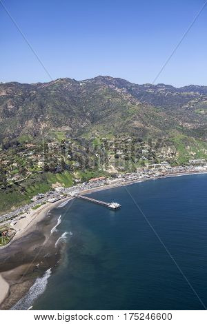 Aerial view of Malibu beaches, homes, pier and Santa Monica Mountains peaks in Southern California.
