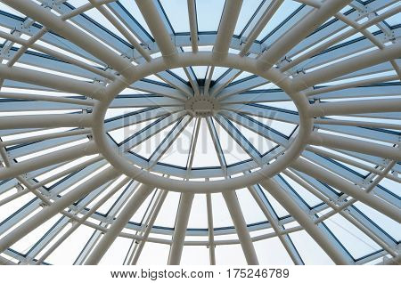 Glass dome of a modern building. View from the inside of the room. Light construction of transparent roof made of round steel tubes. Architectural background
