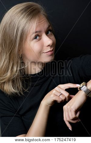 Young blond lady in black T-shirt pointing with finger to wristwatch and smiling